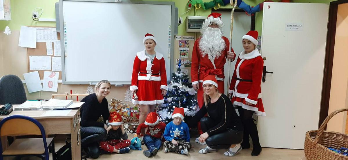 Na zdjęciu widać Mikołaja w towarzystwie Mikołajek i najmłodszych dzieci z oddziału Przedszkolnego Pierwszego. W tle pięknie ustrojona kolorowa choinka. Dzieci uśmiechnięte.