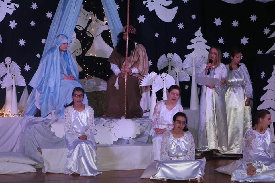 Zdjęcie zrobione jest na sali gimnastycznej, podczas występu Jasełek. Scenografia wykonana przez nauczycieli ukazuje scenerie bożonarodzeniową. Jest szopka w której jest Jezusek na sianku a przy nim Maryja i Józef, w otoczeniu aniołków tych małych, kjtórymi są uczennice naszej szkoły i tych dużych, którymi są Panie nauczycieli naszej szkoły