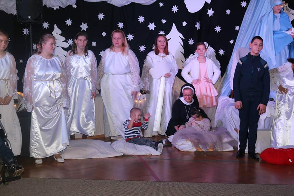 Na zdjęciu ukazana jest scena z Jasełek aniołowie i dzieci z siostra Elwirą