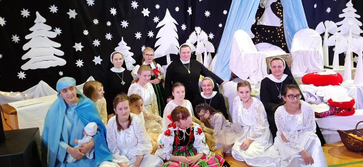 Aniołowie, dzieci, siostry zakonne i Pani w stroju Łowickim w senerii bożonarodzeniowej w przerwie między Jasełkami