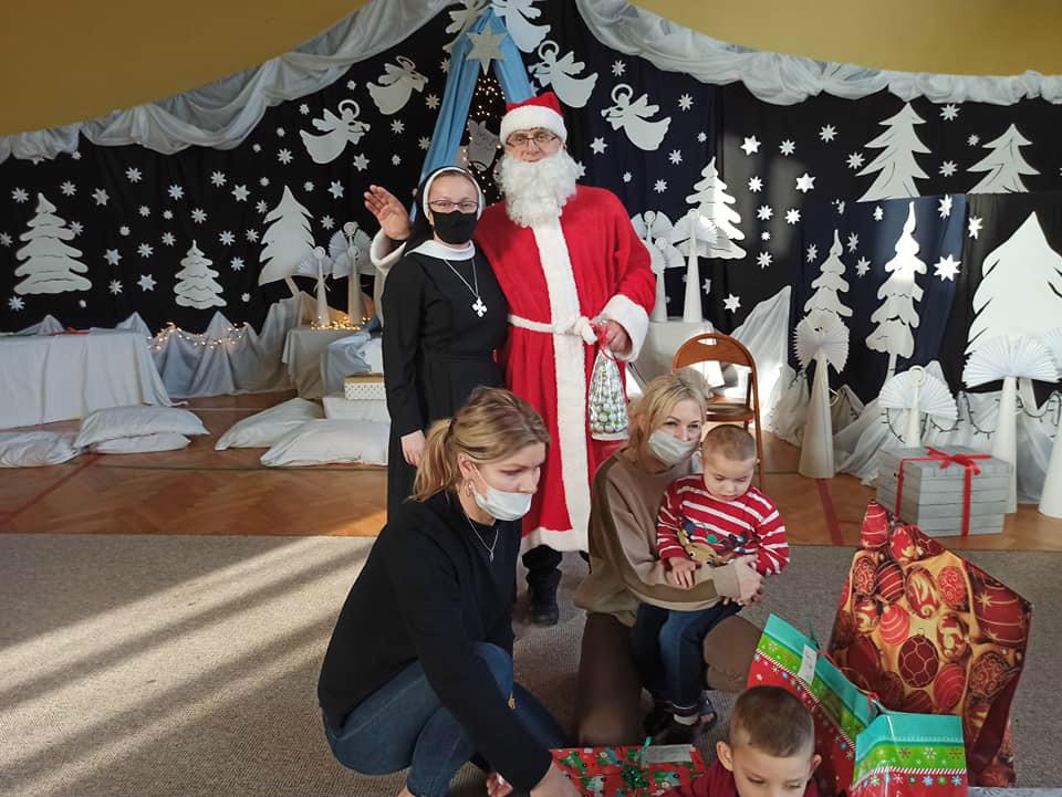Na zdjęciu Siostra Elwira ze świetym Mikołajem w otoczeniu dzieci i pań  z oddziału przedszkolnego, które ogladają prezenty, które otrzymały.