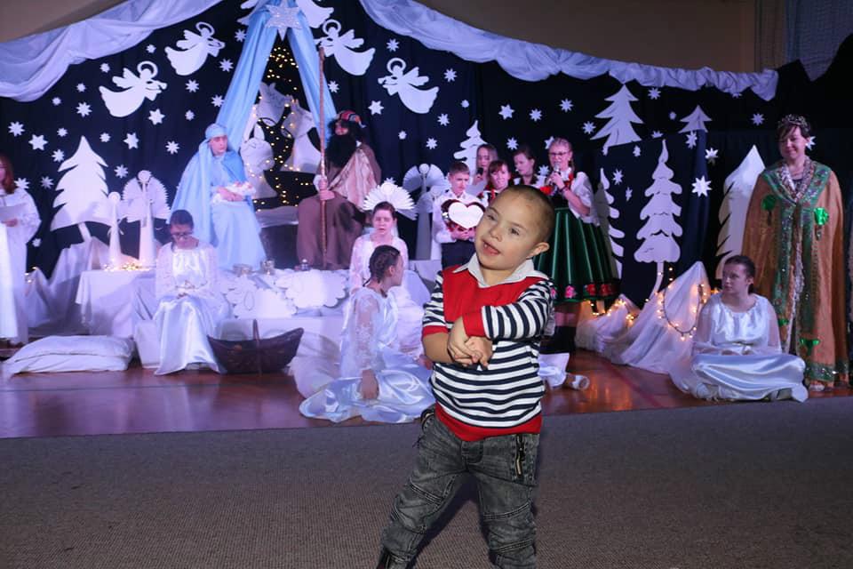 Na zdjęciu ukazana jest scena końcowa jasełek, wszystkie osoby występujące znajdują sie na scenie, mały Kacperek tanczy w rytm kolędy.