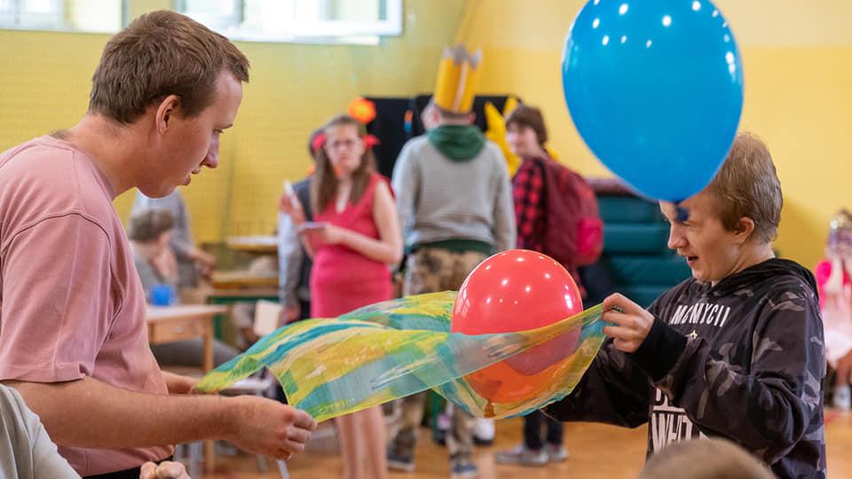 Na zdjęciu są dzieci, które biorą udział w różnych konkurencjach sprawnościowych, zabawa z balonami