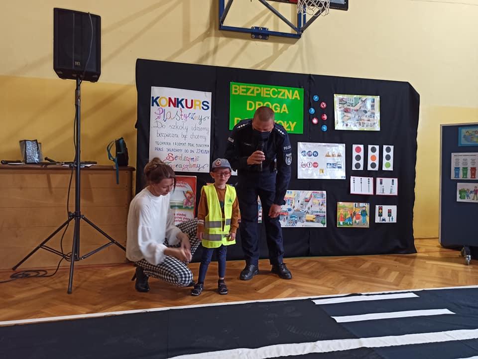 Spotkanie na sali gimnastycznej podczas alelu Bezpieczna droga do szkoły. Pan Policjant wraz z uczniem i panią nauczycielką objaśniają bardzo ważne znaczenie noszenia odblasków