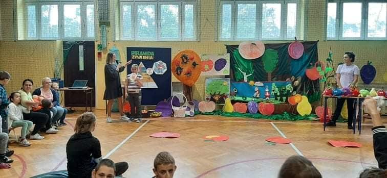 Sala gimnastyczna a naniej dzieci wraz z opiekunami podczas Dnia Jabłka. Dzieci biorą udział w konkurencjach sportowych