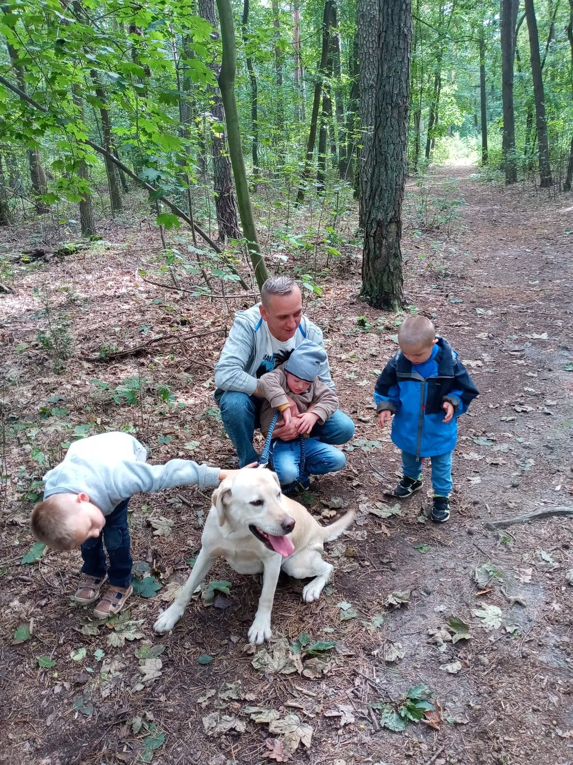 Dzieci wraz z terapeutą na spacerze z psem
