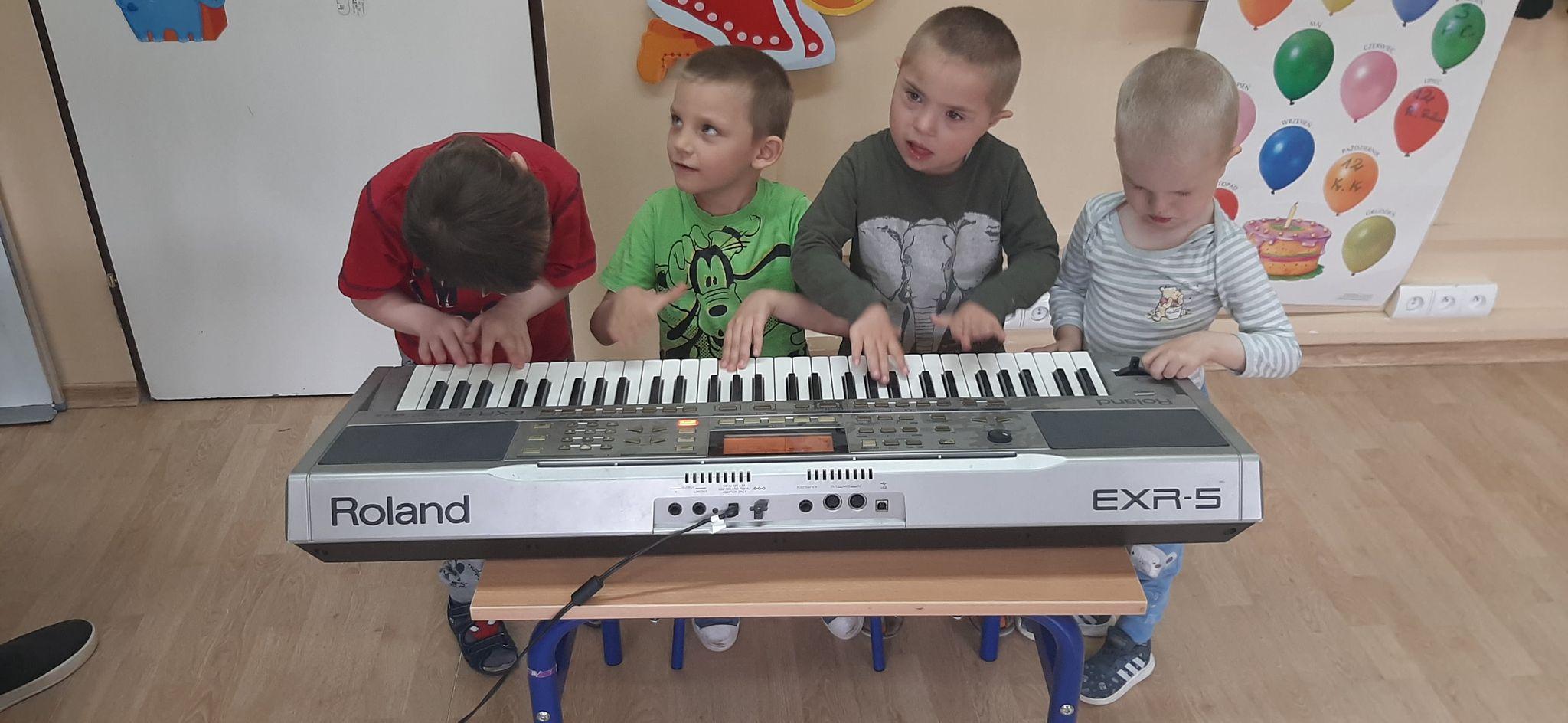 Uczniowie graja na instrumencie klawiszowym