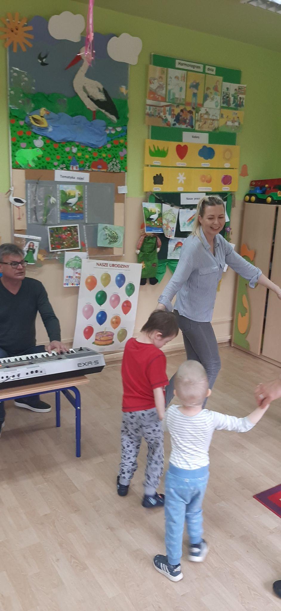 Dzieci wraz z nauczycielem bawią się w kółeczku