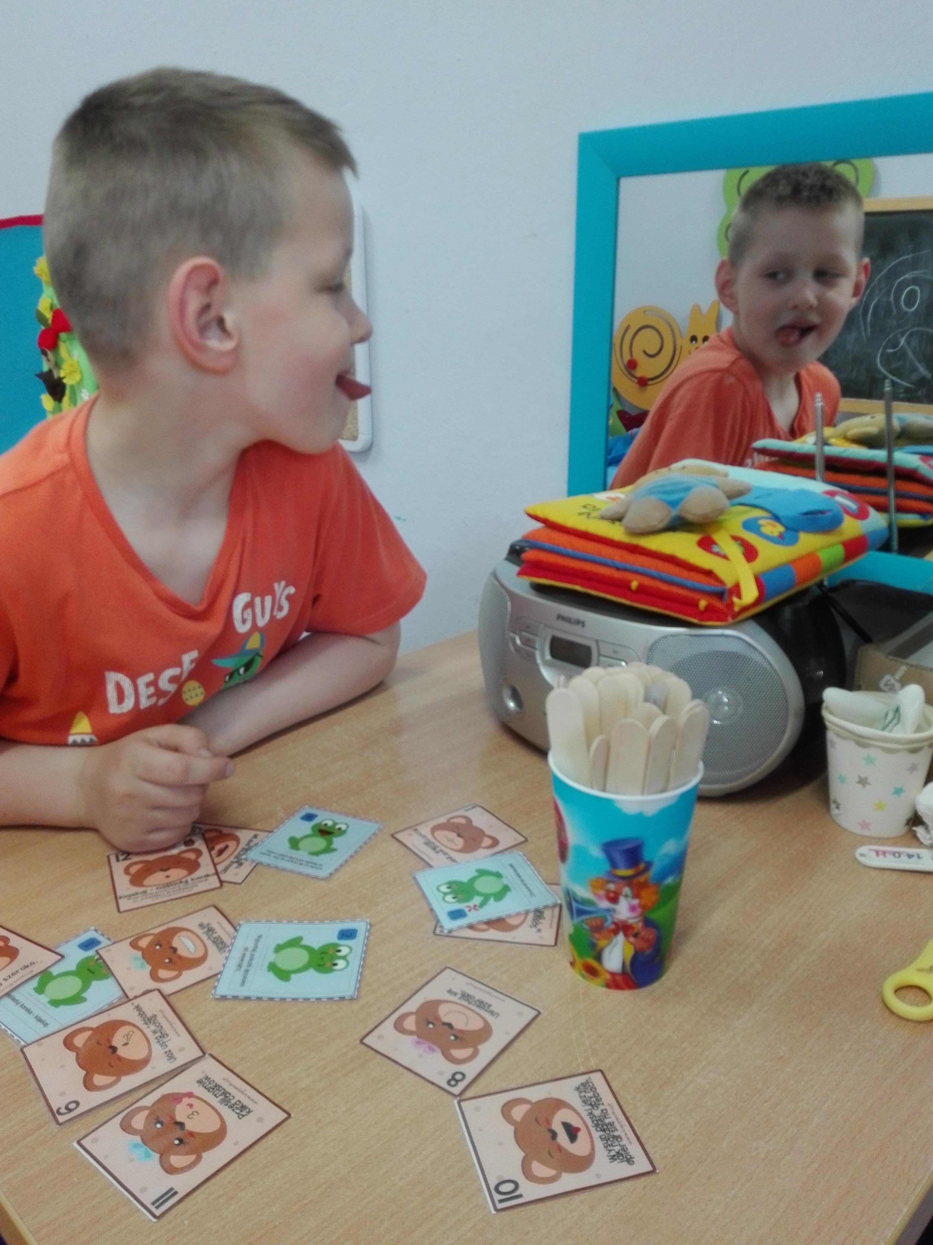 Chłopiec siedzi przed lustrem, języczkiem wykonuje ćwiczenia, a dodatkowo na stoliku jest gra memory