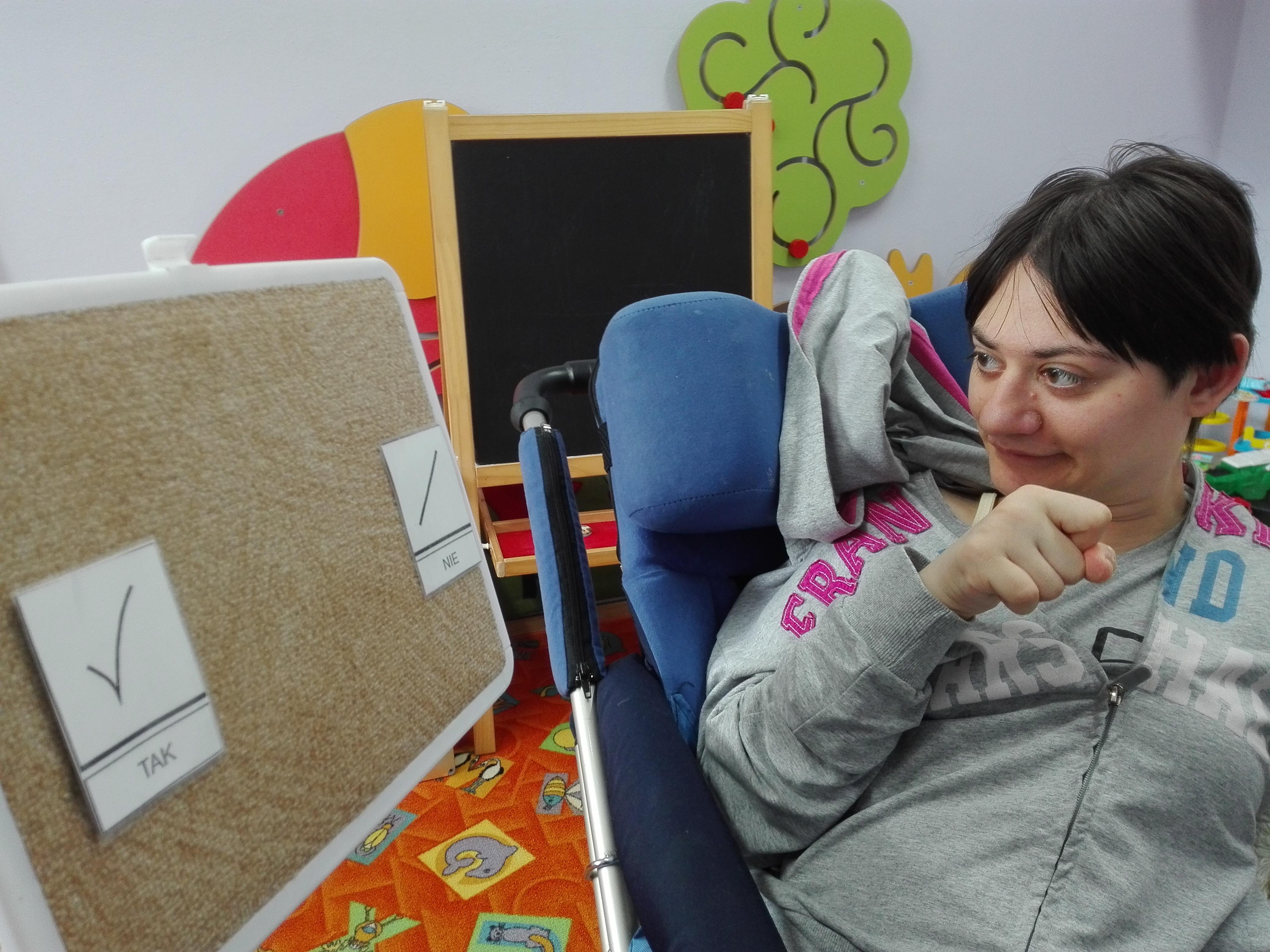 Dziewczynka nie porusza się samodzielnie, siedzi na wózku nauczyciel zadaje pytania na które ma odpowiedzieć tak lub nie wskazująć ręką odpowiedni kartonik