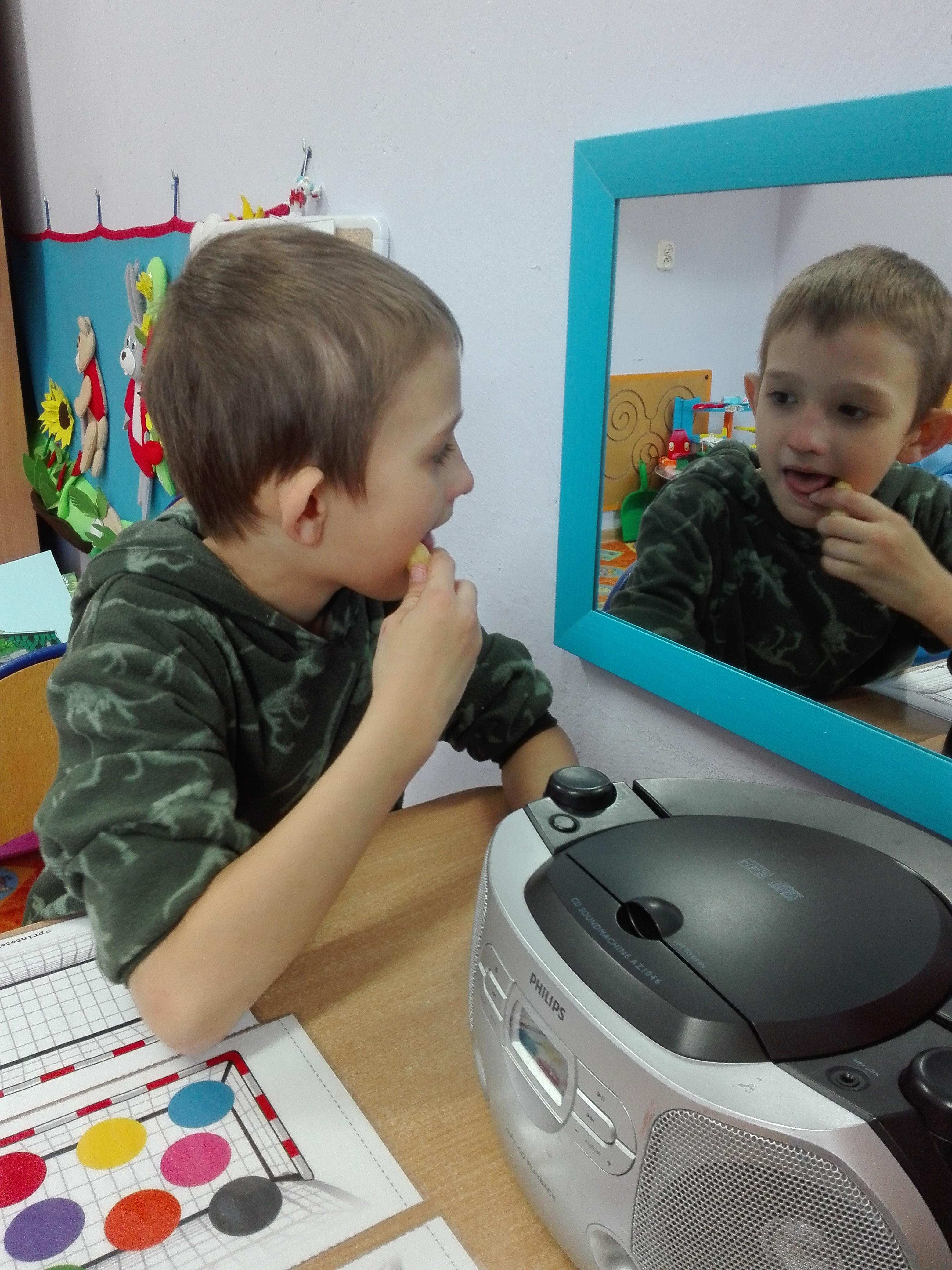 Dziecko siedzi przed lustrem i ma za zadanie naśladować ruchy warg nauczyciela i wykonywać jego polecenia